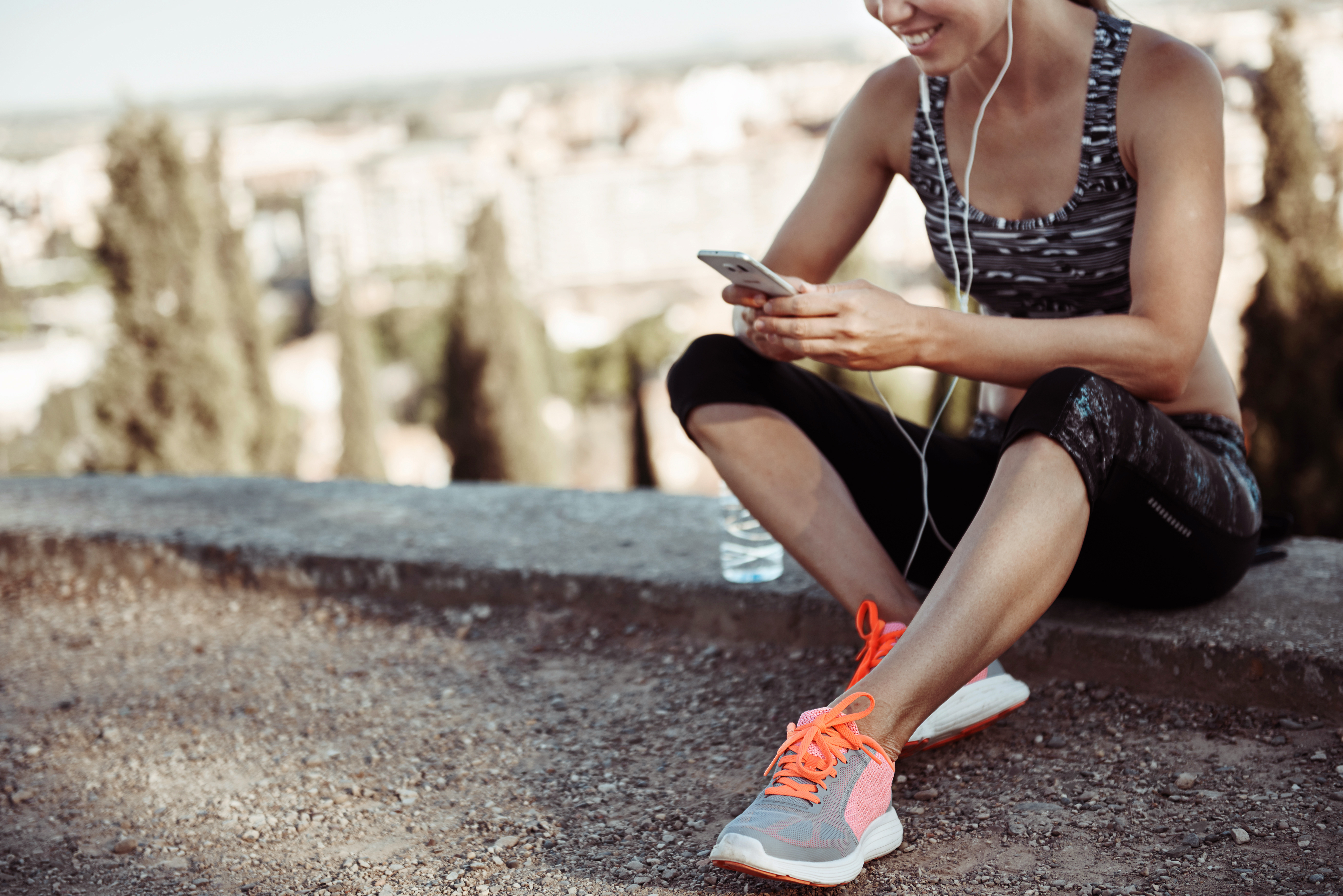 Woman with running shoes listening to music